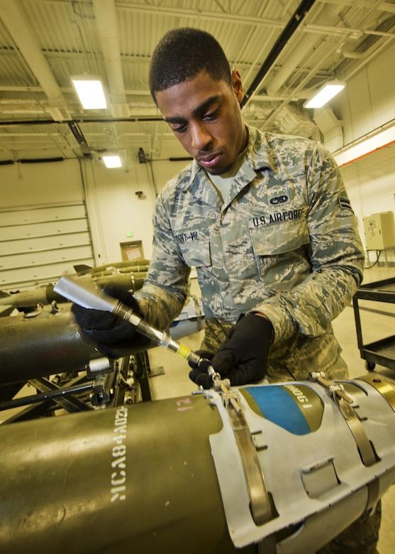 Airman 1st Class Ginseler Saint-Vil, 5th Munitions Squadron line delivery technician, tightens screws on a GBU-38 nose aero-surface assembly at Minot Air Force Base, N.D., Oct. 27, 2016. During bomb building, set screws are tightened to secure the nose aero-surface assembly on an inert 500 lb. MK82 bomb. (U.S. Air Force photo/Airman 1st Class J.T. Armstrong)