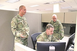 "LEFT TO RIGHT: Sgt. Matthew F. Cundari, Spc. William D. Smith and Chief Warrant Officer 2 Benjamin Koontz, all with the Division Headquarters and Headquarters Battalion, 1st Infantry Division, examine a computer program Oct. 19 in the 1st Inf. Div. headquarters Information Technology office. The three ""Big Red One"" Soldiers each earned first place in individual competitions during the inaugural All-Army Cyberstakes Online Competition Sept. 9 to 18."