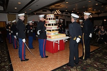 Brig. Gen. John Jansen, Commanding General, 3d Marine Expeditionary Brigade (MEB), and Rear. Adm. Marc H. Dalton, Commander, Amphibious Force 7th Fleet, look on as Marines present a cake in commemoration of the Marine Corps birthday during the 3d MEB Marine Corps ball. The event celebrated the Marine Corps' 241st birthday with a ceremony and dinner. (U.S. Navy photo by Petty Officer 2nd Class Sarah Villegas)