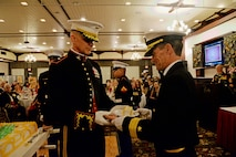 Brig. Gen. John Jansen, Commanding General, 3d Marine Expeditionary Brigade (MEB), passes the first piece of cake to the guest of honor, Rear. Adm. Marc H. Dalton, Commander, Amphibious Force 7th Fleet, as part of tradition during the 3d MEB Marine Corps birthday ball. The event celebrated the Marine Corps' 241st birthday with a ceremony and dinner. (U.S. Navy photo by Petty Officer 2nd Class Sarah Villegas)