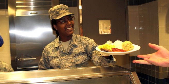 Airman 1st Class Jordan Person serves a Thanksgiving meal with a smile during the November Regularly Scheduled Drill of the 127th Wing, Michigan Air National Guard, at Selfridge Air National Guard Base, Mich., Nov. 5, 2016. Person is a member of the Services Flight of the 127th Force Support Squadron, which presents a Thanksgiving meal to the Airmen of the 127tth Wing every Thanksgiving. (U.S. Air National Guard photo by Tech. Sgt. Dan Heaton)