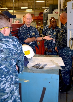 Director of Fleet Maintenance, Rear Adm. Mark Whitney (center) discusses the advantages of Computer Numerically Controlled (CNC) lathes with Senior Chief Tarah Horney (far left) at Southeast Regional Maintenance Center (SERMC) Nov. 1st.