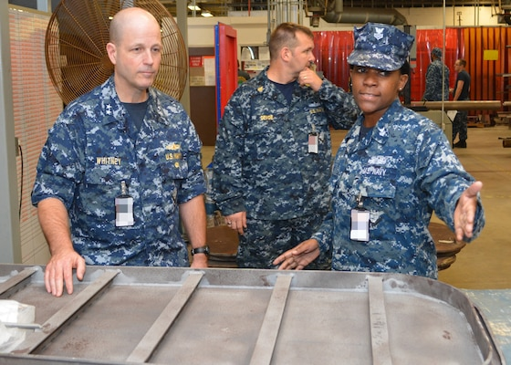 Petty Officer 1st Class Fungai Diura explains to Rear Adm. Mark Whitney, DIrector Fleet maintenance, how damaged watertight doors are repaired at Southeast Regional Maintenance Center in Jacksonville, Fla., Nov. 1st.