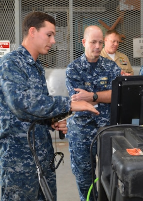 Petty Officer 3rd Class Mitchell Lafave explains the functionality of a surface-supplied camera equipment to Rear Adm. Mark Whitney at Southeast Regional Maintenance Center in Jacksonville, Fla., Nov. 1st. Rear Adm. Whitney is the Director, Fleet Maintenance under Fleet Forces Command. The camera transmits high quality video from divers working underwater which is displayed and captured digitally on the surface.