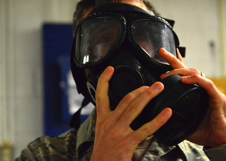 U.S. Air Force Tech. Sgt. Christopher Stahl, Air Combat Command, Heritage of America Band bassoonist, dons a gas mask and checks seal during the German Armed Forces Badge for military Proficiency event at Joint Base Langley-Eustis, Va., Nov. 2, 2016.  The GAFPB includes a pass or fail nuclear, biological, chemical evaluation of donning a protective mask within nine seconds.  (U.S. Air Force photo/Tech Sgt. Daylena S. Ricks)