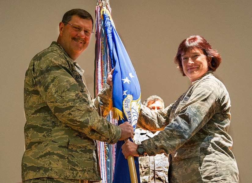 315th Airlift Wing Commander, Col. Gregory Gilmour passes the guidon to new 315th Maintenance Group Commander, Col. Sharon Johnson Nov. 6.  Members of the 315th Maintenance Group welcomed the new commander to their unit during a change of command ceremony at Joint Base Charleston, South Carolina. Col. Richard Gay relinquished his command of seven years to Johnson as Gay prepares for his retirement later in the year. (U.S. Air Force Photo by Senior Airman Jonathan Lane)
