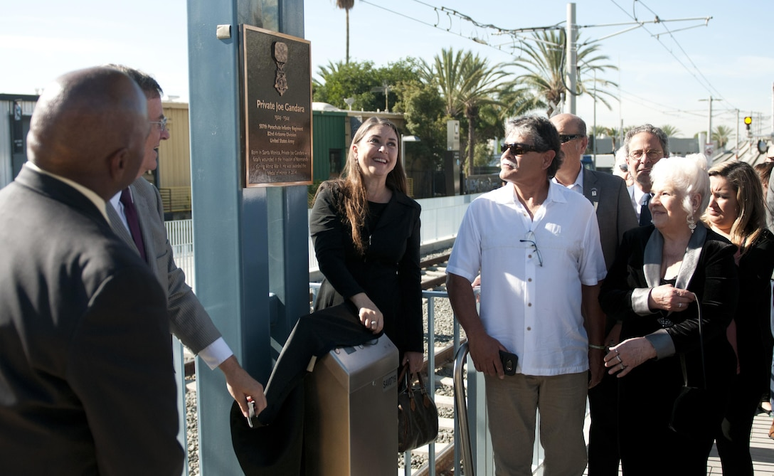 Hannah Adams, center, the great-niece of Pvt. Joe Gandara, helps unveil a plaque at the Santa Monica 26th Street/Bergamot train station dedicated to her great-uncle Nov. 4, along with other Gandara family members, Santa Monica Mayor Tony Vazquez, and Los Angeles County Metropolitan Transportation Authority Chief Executive Officer Phillip Washington. Gandara, killed in action in WWII, was awarded the Medal of Honor in 2014 as part of the Valor 24 program. (U.S. Army Photo by Sgt. 1st Class Alexandra Hays, 79th Sustainment Support Command).