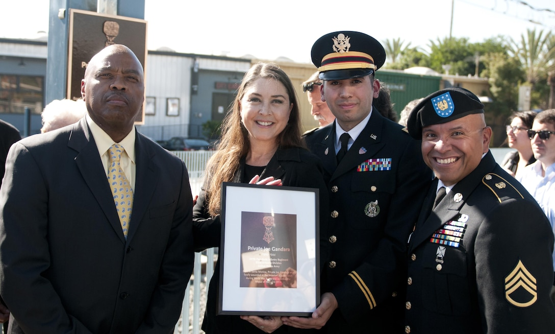 From left to right: Los Angeles County Metropolitan Transportation Authority Chief Executive Officer Phillip Washington, the great-niece of Pvt. Joe Gandara Hannah Adams, Capt. Christopher Montes of the Los Angeles Recruiting Battalion, and U.S. Army Public Affairs film & television liasion Staff. Sgt. John Mattias celebrate the unveiling of a plaque at the Santa Monica 26th Street/Bergamot train station dedicated to Gandara Nov. 4. Gandara, killed in action in WWII, was awarded the Medal of Honor in 2014 as part of the Valor 24 program. (U.S. Army Photo by Sgt. 1st Class Alexandra Hays, 79th Sustainment Support Command).