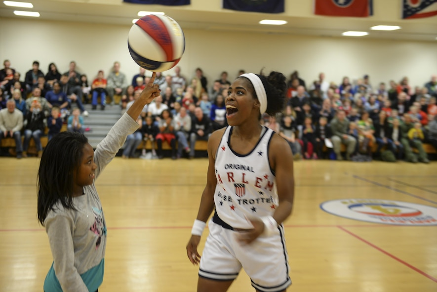 Harlem Globetrotters guard, TNT, watches a volunteer spin a basketball on her finger Nov. 4, 2016, at the Hardstand Fitness Center on RAF Mildenhall, England. Throughout the performance, audience members were selected to participate in the show. (U.S. Air Force photo by Staff Sgt. Micaiah Anthony)