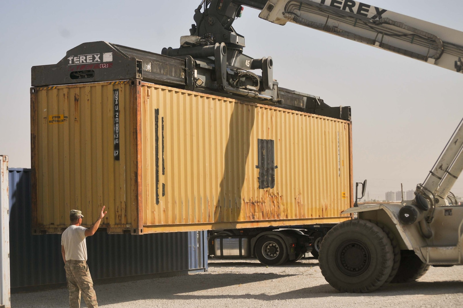 In this file photo taken Sept. 3 2016, U.S. Army Sgt. Robert Wheeler, 336th Combat Support Sustainment, directs a crane repositioning a container, in Erbil, Iraq. The 336th CCSB's  material handling equipment team helps move supplies for coalition forces in Erbil, and works with the support operations cell of the 526th Brigade Support Battalion, Task Force Strike to sustain operations in northern Iraq. (U.S. Army photo by 1st Lt. Daniel Johnson)