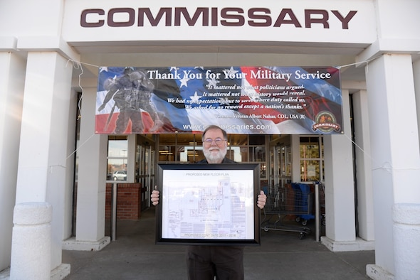 Mr. James Freeman, commissary store director, stands in front of the commissary entrance displaying renovation floor plans at F.E. Warren Air Force base, Wyo., Nov. 8, 2016.  The commissary renovations will provide an enhanced shopping experience to customers and is scheduled to be completed in late 2018.