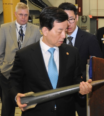 Republic of Korea (ROK) Minister of National Defense Han Min-koo – who led the ROK delegation to see new and emerging technologies developed at Naval Surface Warfare Center Dahlgren Division (NSWCDD) – holds an electromagnetic railgun projectile and inspects damage caused to metal plates from a previous test. NSWCDD engineers briefed Han and his delegation on electromagnetic launchers, hypervelocity projectiles, and directed energy weapons, in addition to the command's core capabilities in complex warfare systems development and integration to incorporate electric weapons technology into existing and future fighting forces and platforms.
