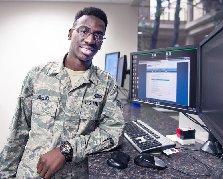 U.S. Air Force Senior Airman Michael Mwelwa, 60th Comptroller Squadron, poses for a photo by his workstation at Travis Air Force Base, Calif., Oct. 25, 2016. Mwelwa was recently awarded U.S. citizenship after coming to the United States at the age five from The Republic of Zambia. (U.S. Air Force photo/Louis Briscese)