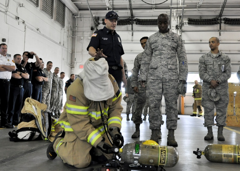 Kristofer Maynard, 92nd Civil Engineer Squadron firefighter, explains to Brig. Gen. Stacey Hawkins, Air Mobility Command director of logistics, engineering and force protection, some of the training firefighters go through during a base tour Nov. 7, 2016, at Fairchild Air Force Base, Wash. One aspect of firefighter training is putting an oxygen tank together and equipping it while blindfolded. (U.S. Air Force photo/Airman 1st Class Taylor Shelton)