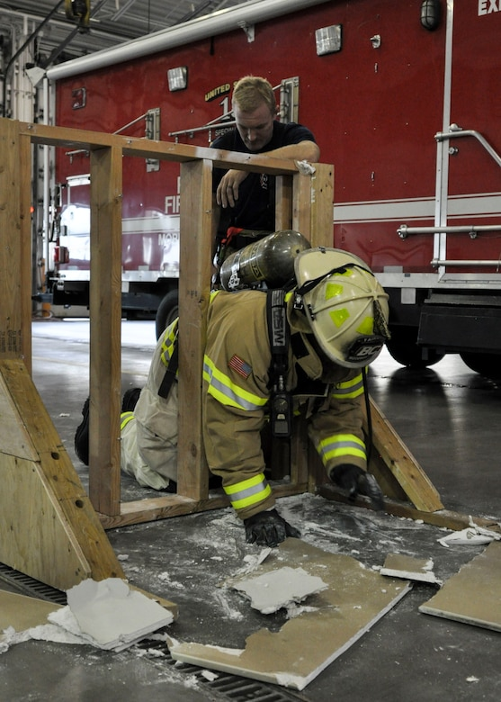 Brig. Gen. Stacey Hawkins, Air Mobility Command director of logistics, engineering and force protection, crawls through a 16-inch cut out during a base tour Nov. 7, 2016, at Fairchild Air Force Base, Wash. The 92nd Civil Engineer Squadron Fire Department put on a demonstration showcasing the training they do, allowing Hawkins to participate in a portion at the end. (U.S. Air Force photo/Airman 1st Class Taylor Shelton)