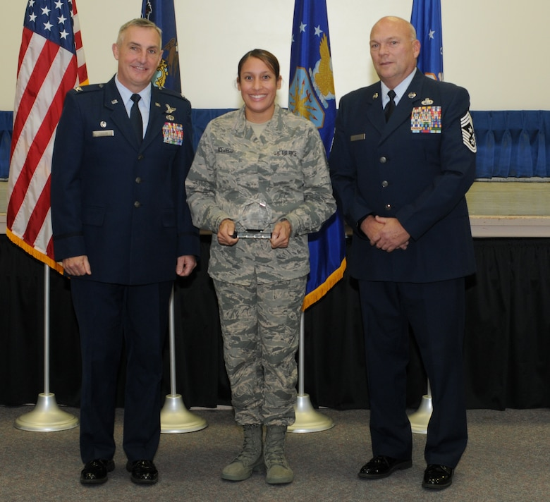 Master Sgt. Talitacumi Acevedo, the 111th Attack Wing recruiting and retention manager, stands with 111th ATKW Commander Col. Howard Eissler and Wing Command Chief Master Sgt. Paul Frisco while receiving the Fiscal Year 2015 State Award at Horsham Air Guard Station, Pa., on November 6, 2016. Acevedo received the State Recruiting and Retention Manager (RRM) of the Year award for being the top RRM in the state with superior retention programs and 20 total accessions. The award symbolizes a commitment to the making sure the Air National Guard obtains and retains quality members who will be an asset to the mission. (U.S. National Guard photo by Senior Airman Timi Jones)