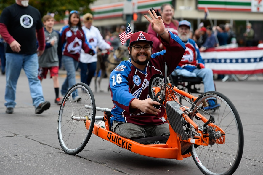 Jerry Devaul, a wounded veteran, rides a modified bicycle in procession during the Colorado Springs Veteran's Day Parade