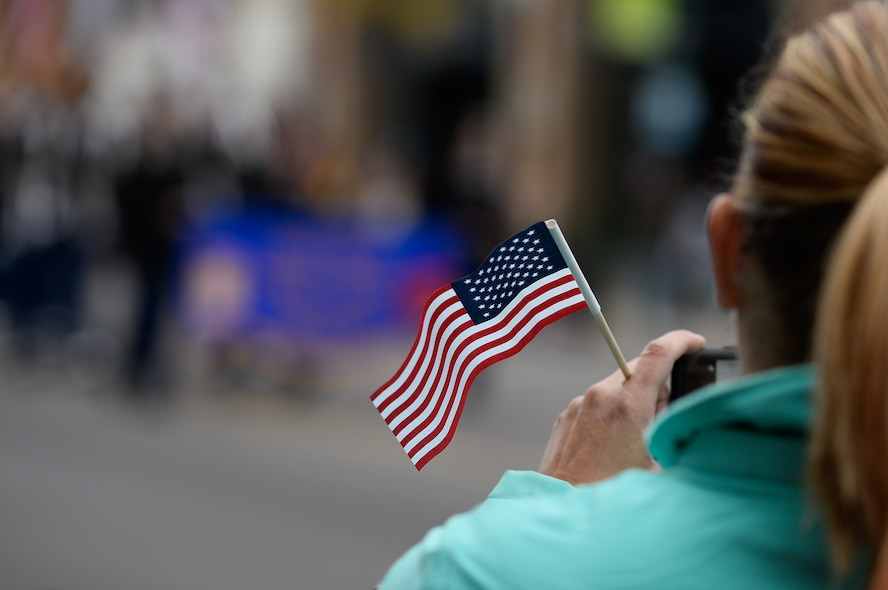 A woman taking a photo of the parade holds a small american flag