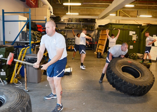 During the one hour workout, Airmen from the 445th Security Forces Squadron workout using duty equipment to perform functional movements, including a shoulder press with a medical litter, sledgehammer strikes and a tire flip. (U.S. Air Force photo/Staff Sgt. Rachel Ingram)