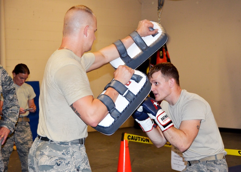 445th Security Forces Squadron Airmen Tech. Sgt. Chris Booth, left, and Staff Sgt. Jake McCorkle practice their combatives skills using squadron equipment in the newly-renovated bay exercise area. The two Citizen Airmen host monthly martial arts workouts on the evening before UTA begins. (U.S. Air Force photo/Staff Sgt. Rachel Ingram)