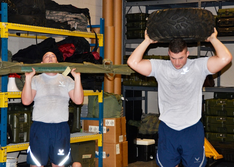 Airmen from the 445th Security Forces Squadron workout using duty equipment to perform functional movements, like a shoulder press with a medical litter and vehicle tire. The innovative program was designed by Staff Sgt. Shayne Denihan. (U.S. Air Force photo/Staff Sgt. Rachel Ingram)