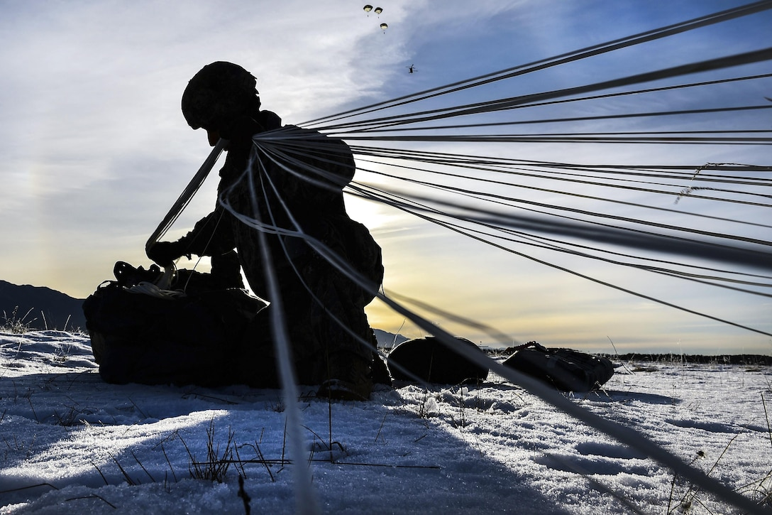 Army Spc. Wesley Madera-Lopez pulls parachute straps while recovering his chute and equipment after airborne training onto Malemute drop zone at Joint Base Elmendorf-Richardson, Alaska, Nov. 3, 2016. Madera-Lopez is assigned to the 25th Infantry Division's Company B, 6th Brigade Engineer Battalion (Airborne), 4th Infantry Brigade Combat Team (Airborne), Alaska. Air Force photo by Justin Connaher