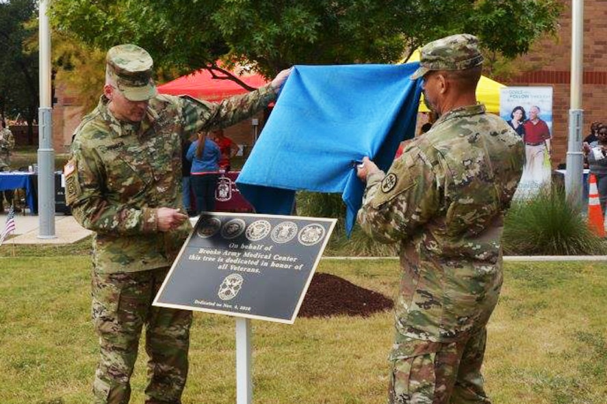 Brooke Army Medical Center Commanding General Army Brig. Gen. Jeffrey Johnson and Command Sgt. Maj. Albert Crews unveil a temporary marker to dedicate an oak tree