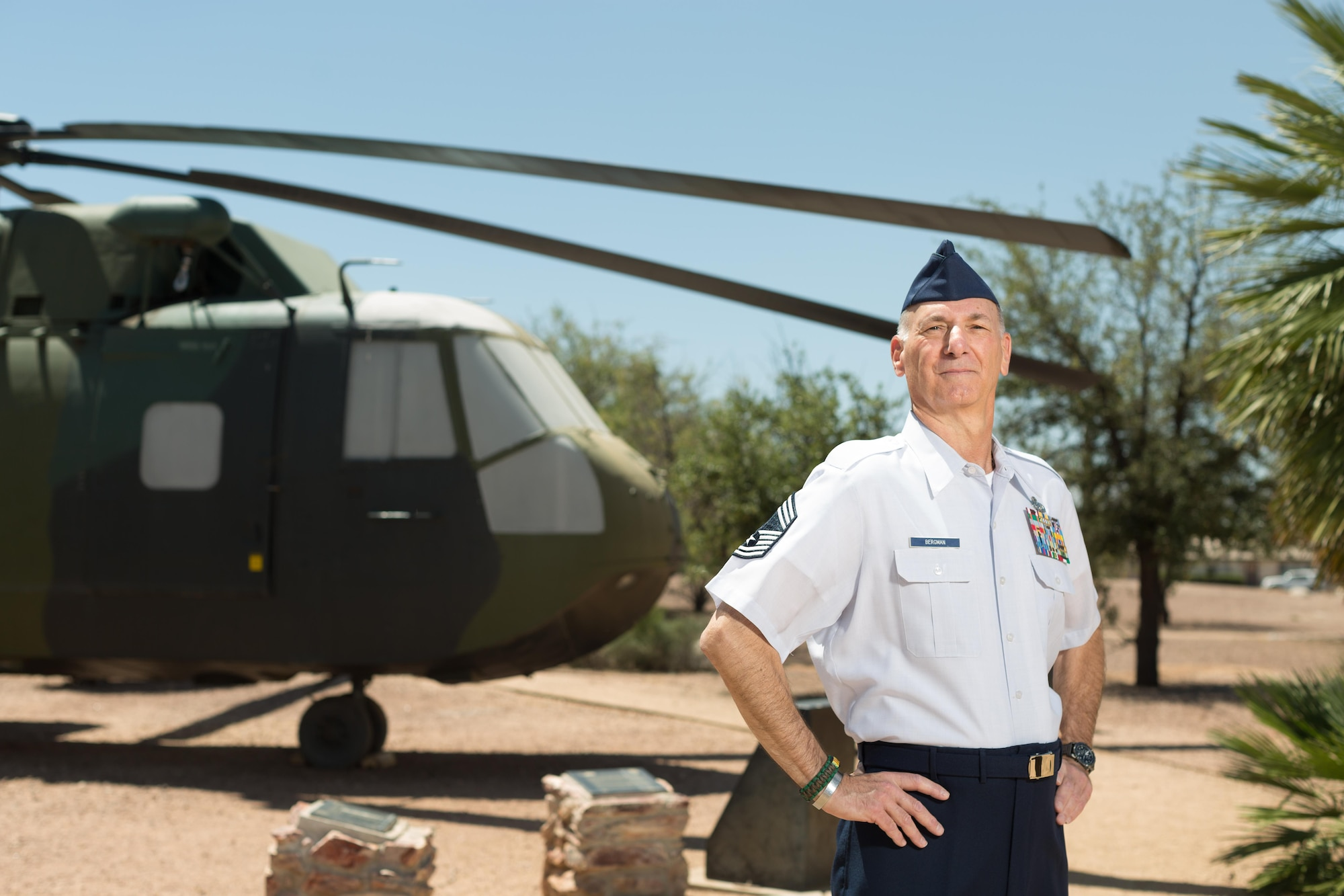 """Retired Chief Master Sgt. Craig Bergman stands in front of the HH-3 """"Jolly Green Giant"""" at Davis-Monthan Air Force Base, Ariz., May 19, 2016. Bergman retired as the maintenance superintendent for the 943rd Maintenance Squadron in 2007, having been one of five U.S. Air Force Reserve Airmen to establish the 71st Special Operations Squadron and bring the HH-3 here. His family's military legacy dates back to World War I. (U.S. Air Force photo by Tech. Sgt. Carolyn Herrick)"""