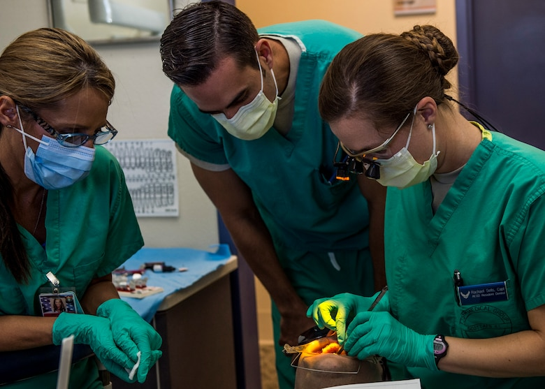 Maj. David Servello, chief of orthodontics, overseas the work of Capt. Rachael Sells as she conducts an operation giving a patient braces, Scott Air Force Base, Ill., Oct. 25, 2016. Sells is one of four residents in the Advanced Education in General Dentistry Program.