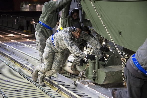 Airman Jerry Booker, 60th Aerial Port Squadron, pushes a U.S. Army Bridge Erection Boat (BEB) onto a C-5M Super Galaxy May 7, 2016, at Travis Air Force Base, Calif. The 60th APS successfully uploaded multiple BEBs onto the aircraft where they were transported to Iraq in support of Operation Inherent Resolve. (U.S. Air Force by Staff Sgt. Charles Rivezzo)
