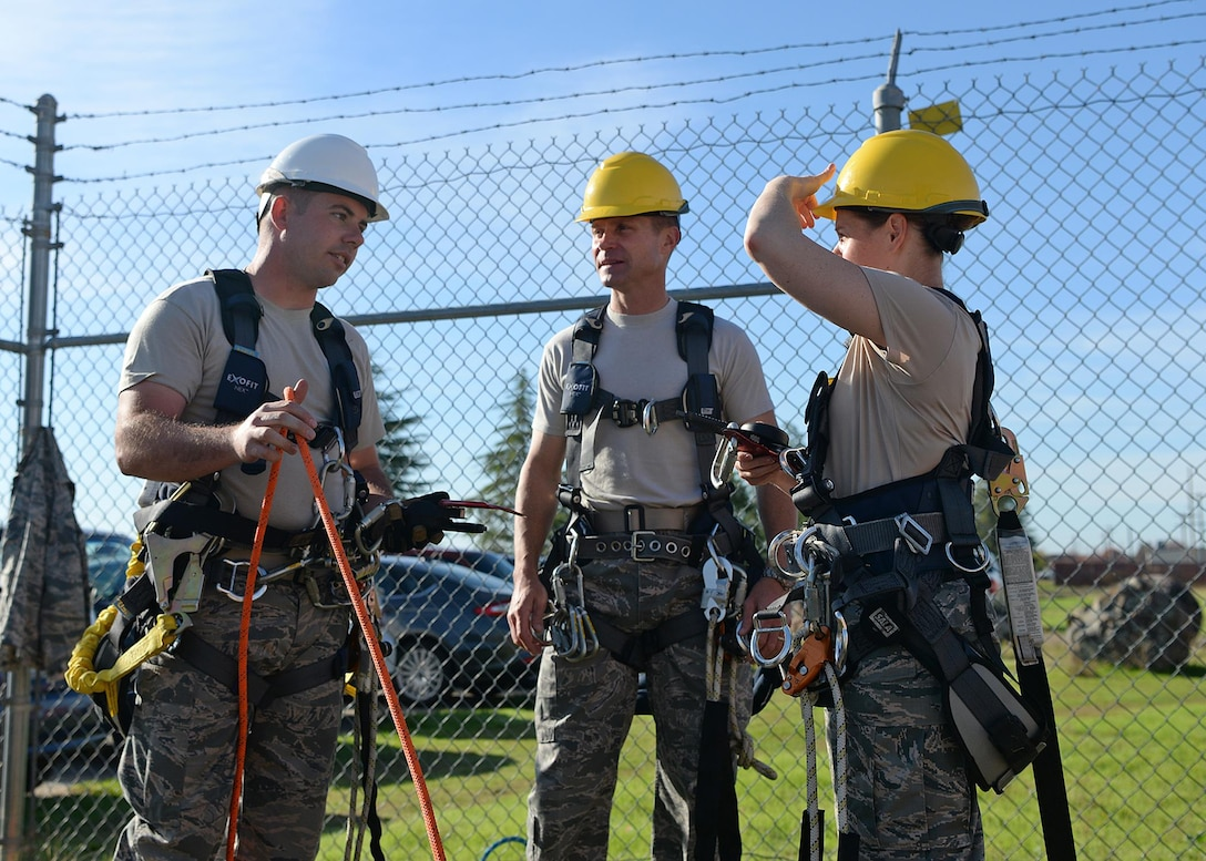 Tech. Sgt. Joshua Donahue, 9th Communication Squadron cable and antenna maintainer, explains the purpose of safety equipment required for climbing to Col. Larry Broadwell, 9th Reconnaissance Wing commander, and Chief Master Sgt. Jessica Bender, 9th RW command chief, before they climb a communication tower Nov. 8, 2016, at Beale Air Force Base, California. Broadwell and Bender went through training to gain a better perspective of what Airmen experience when climbing towers. (U.S. Air Force photo/Airman Tristan D. Viglianco)