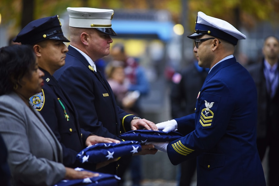 Army veteran Joseph Duggan Jr., a New York Fire Department battalion chief, accepts an American flag