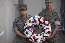 Basic High School Marine Corps Junior ROTC cadets carry a wreath to be placed in front of a Veterans Deceased Panel with the names inscribed of all deceased service members that resided in Henderson, Nev. during the city's Veterans Day celebration, Nov. 5.  All attendees walked to the Veterans Memorial Wall to join in the celebration. (U.S. Air Force photo by Lawrence Crespo)