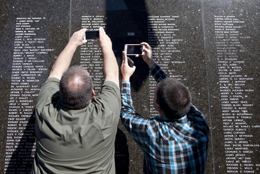 Family members take photos of their loved one's name inscribed on the City of Henderson, Nev. Veterans Memorial Wall during a Veterans Day celebration, Nov. 5.  Names are etched onto the black marble wall to memorialize Henderson residence who served to keep our nation free. (U.S. Air Force photo by Lawrence Crespo)