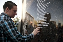 A family member reflects after viewing a loved one's name inscribed on the City of Henderson, Nev. Veterans Memorial Wall during a Veterans Day celebration, Nov. 5.  Each year Henderson city leaders are joined by those who have served our country, those who continue the fight, and families and friends of veterans to celebrate the lives and actions of our military personnel in protecting this great nation. (U.S. Air Force photo by Lawrence Crespo)