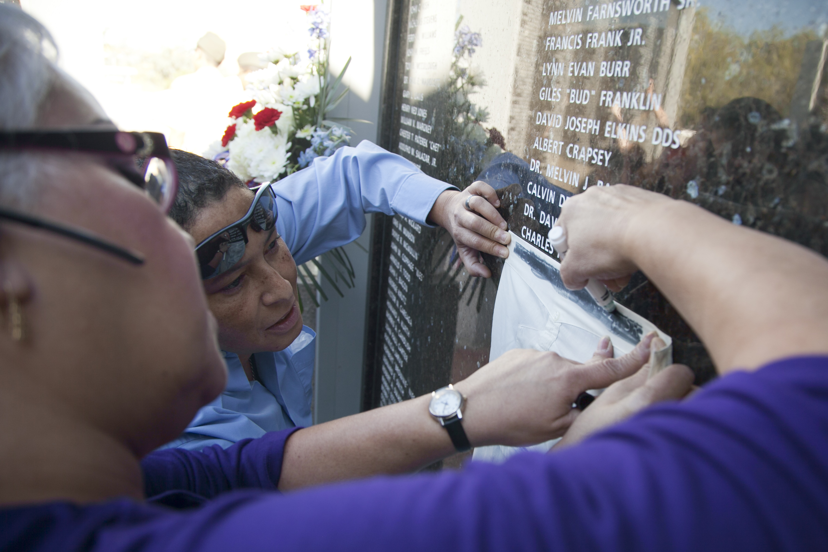 Members from the Martinez family outline their brother's name inscribed on the Veterans Deceased Panel