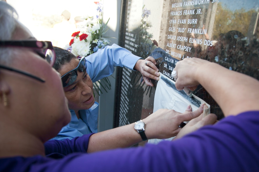 Members from the Martinez family outline their brother's name inscribed on the Veterans Deceased Panel during a Veterans Day celebration in Henderson, Nev., Nov. 5. Air Force photo by Lawrence Crespo