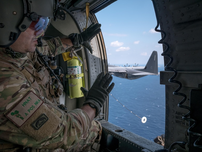 U.S. Air Force Master Sgt. Vincent Hnat, 33rd Rescue Squadron special mission aviator, communicates with aircrew on a MC-130J Commando II from the 17th Special Operations Squadron off the coast of Okinawa, Japan. During the training, members of the 33rd RQS performed an array of maneuvers and procedures to include helocasting, a simulated downed pilot in a hostile environment and helicopter air-to-air refueling. (U.S. Air Force photo by Senior Airman John Linzmeier)
