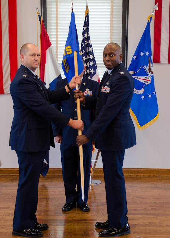 Col. William Boothman, 157th Air Operations Group commander, hands the unit guidon, and with it, leadership authority, to Col. Chip Atterbury, 157th Air Intelligence Squadron commander, at Jefferson Barracks Air National Guard Base, Missouri, during drill Nov. 5, 2016. Three new commanders took charge of three new squadrons -- the 157th AIS, the 157th Combat Operations Squadron and the 157th Air Communications Squadron, new units of the 157th AOG -- at a single assumption of command ceremony. (U.S. Air National Guard photo by Staff Sgt. Brittany Cannon)