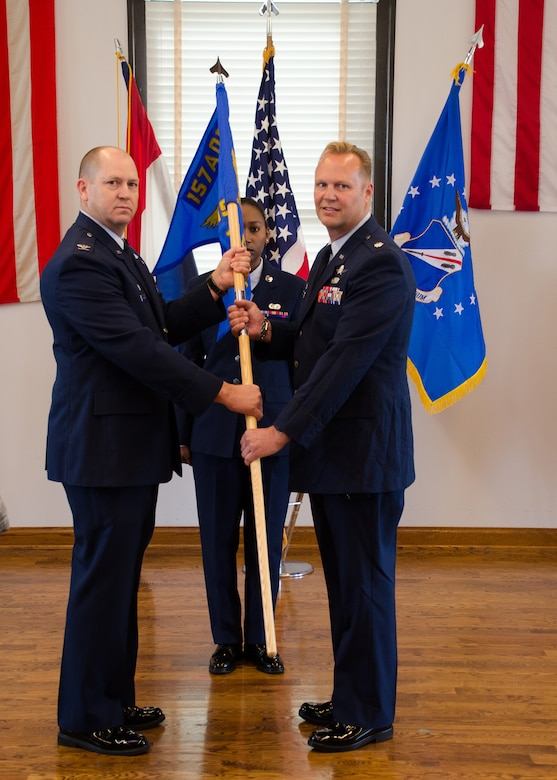 Col. William Boothman, 157th Air Operations Group commander, hands the unit guidon, and with it, leadership authority, to Lt. Col. Thomas Bischoff, 157th Air Communications Squadron commander, at Jefferson Barracks Air National Guard Base, Missouri, during drill Nov. 5, 2016. Three new commanders took charge of three new squadrons -- the 157th ACS, the 157th Air Intelligence Squadron and the 157th Combat Operations Squadron, new units of the 157th AOG -- at a single assumption of command ceremony. (U.S. Air National Guard photo by Staff Sgt. Brittany Cannon)