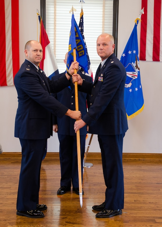 Col. William Boothman, 157th Air Operations Group commander, hands the unit guidon, and with it, leadership authority, to Lt. Col. James Hendren, 157th Combat Operations Squadron commander, at Jefferson Barracks Air National Guard Base, Missouri, during drill Nov. 5, 2016. Three new commanders took charge of three new squadrons -- the 157th COS, the 157th Air Intelligence Squadron and the 157th Air Communications Squadron, new units of the 157th AOG -- at a single assumption of command ceremony. (U.S. Air National Guard photo by Staff Sgt. Brittany Cannon)