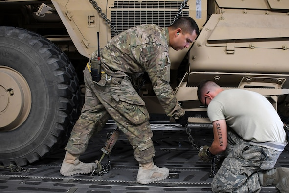 Tech Sgt. Ronald Gowen, a 387th Air Expeditionary Squadron logistician, left, helps Staff Sgt. Dylan Collins, a 386th Expeditionary Logistics Readiness Squadron aerial porter, right, with securing a mine-resistant ambush-protected vehicle in the cargo area of a C-17 Globemaster III at an undisclosed location in Southwest Asia Nov. 4, 2016. Gowen is currently embedded with  the 386th Expeditionary Logistics Readiness Squadron as he awaits transfer to a joint unit.