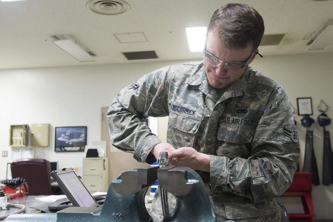 Airman 1st Class Hudson McCormick, 374th Maintenance Squadron aircraft hydraulics journeyman, tightens a bolt onto a hose in preparation for testing at Yokota Air Base, Japan, Nov. 8, 2016. Each length of hose is tested before use to ensure that there are no defects. (U.S. Air Force photo by Senior Airman David C. Danford/Released)