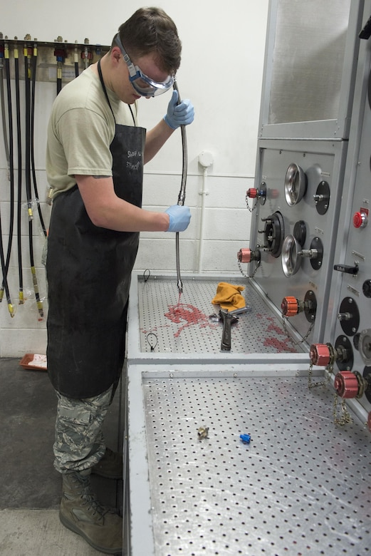 Airman 1st Class Hudson McCormick, 374th Maintenance Squadron aircraft hydraulics journeyman, drains hydraulics testing fluid from a hose at Yokota Air Base, Japan, Nov. 8, 2016. The hydraulics shop is part of the accessories flight which also includes the fuels maintenance and electrical and environmental shops. (U.S. Air Force photo by Senior Airman David C. Danford/Released)