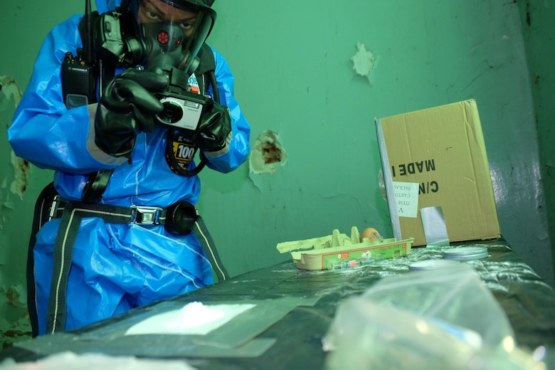 """U.S. Army Staff Sgt. Camille Foggy a survey team chief with the 773rd Civil Support Team, 7th Mission Support Command takes a photo of a suspected chemical compound Nov. 2, 2016, during the NATO EADRCC Consequence Management Field Exercise """"CRNA GORA 2016."""""""