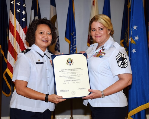Col. Imelda Reedy, 14th Medical Group Commander, presents Chief Master Sgt. Brandi Thomas, 14th MDG Superintendent, with her certificate of retirement Nov. 4 at Columbus Air Force Base, Mississippi. Thomas served for 23 years in the military. (U.S. Air Force photo by Sharon Ybarra)