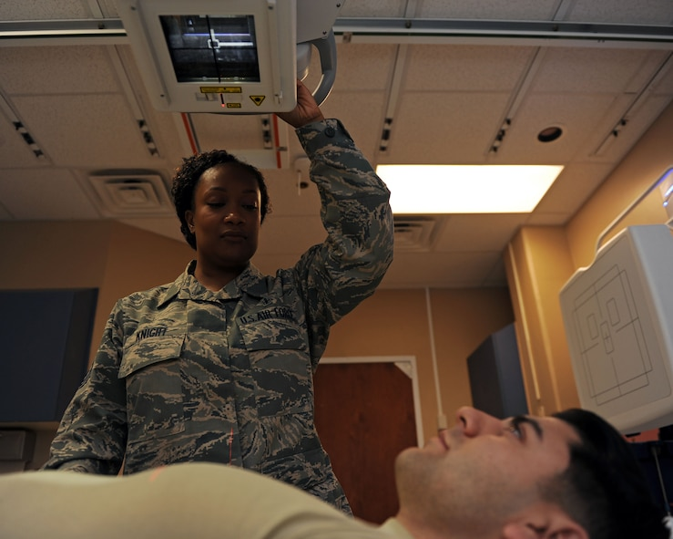 Tech. Sgt. Anissa Knight, 27th Special Operations Medical Support Squadron NCO-in charge of diagnostic imaging, simulates taking an X-ray with the assistance of Senior Airman Efren Armenta Herrera, 27th SOMDSS diagnostic imagining technologist, at 27th Special Operations Medical Group, Oct. 25, 2016. Diagnostic imaging technologists assist physicians by taking comprehensive X-rays of afflicted body parts in settings ranging from surgery centers to imaging rooms. These professionals utilize highly sophisticated equipment and an intimate knowledge of human anatomy to help generate reliable imagery and treat their patients. (U.S. Air Force photo/Staff Sgt. Whitney Amstutz/released)