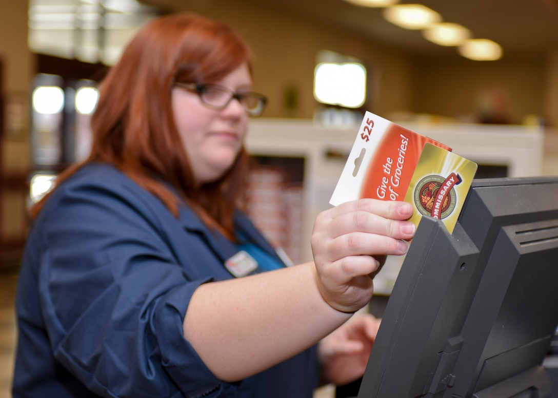 Sarah Croston, a cashier at the Commissary, swipes a gift card at Ellsworth Air Force Base, S.D., on Nov. 8, 2016. Croston, who has assisted the First Sergeant's Council with Operation Warm Heart for the last four years, helped the First Sergeants' Council purchase $2,500.00 worth of Commissary gift cards that they will later give to Airmen in need. (U.S. Air Force photo by Airman 1st Class Randahl J. Jenson)