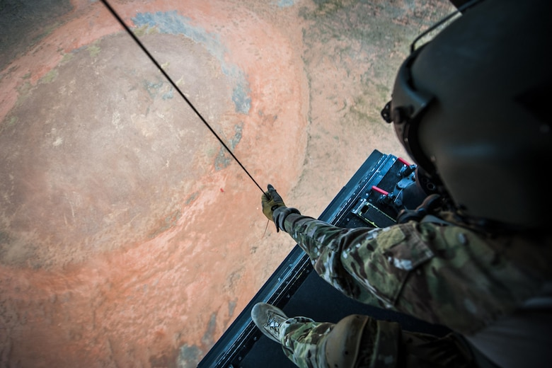 A flight engineer with the 8th Special Operations Squadron operates the hoist of a CV-22 Osprey tiltrotor aircraft above the Eglin Range, Fla., Nov. 8, 2016. The Osprey has been used operationally since 2006 to conduct long-range infiltration, exfiltration and resupply missions for special operations forces globally. (U.S. Air Force photo by Airman 1st Class Joseph Pick)
