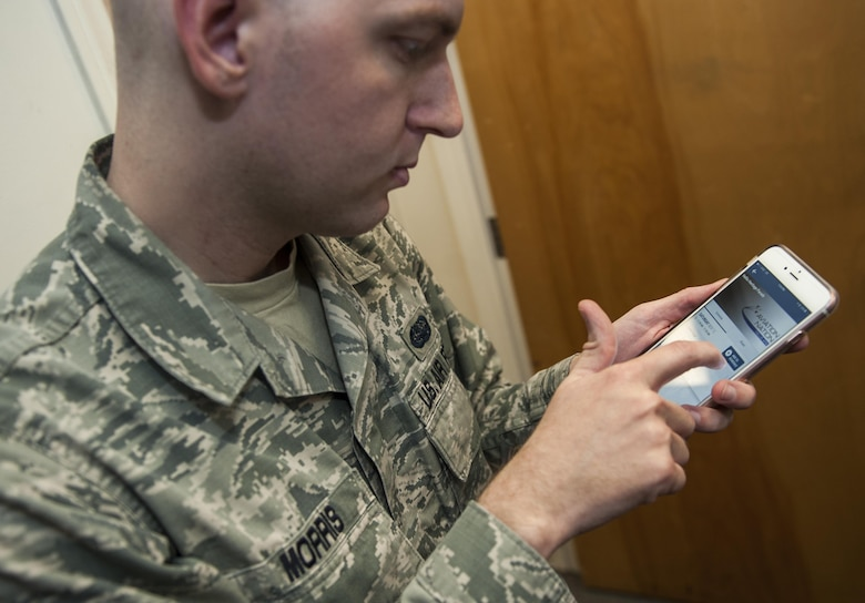 Staff Sgt. Michael Morris, 99th Communications Squadron base content manager, demonstrates how to use the Aviation Nation application that he created for the air show on Nellis Air Force Base, Nev., Nov. 9, 2016. The app has several features and provides up to date information encompassing what is going on during the air show with the ease of it being on a smart phone or tablet. (U.S. Air Force photo by Airman 1st Class Kevin Tanenbaum/Released)